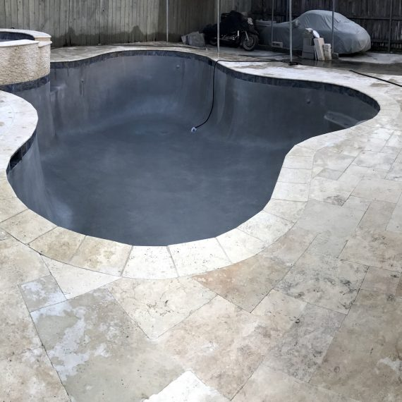 New Orleans Pool Repair project with Concrete deck removed and french pattern travertine pavers